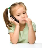 11554969-cute-little-girl-is-talking-on-a-cell-phone-while-sitting-at-table-isolated-over-white