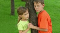 stock-footage-two-kids-brother-and-little-sister-hold-hands-near-tree-and-talk