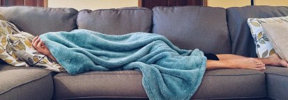 Someone-laying-on-the-couch-underneath-a-blanket_pexel